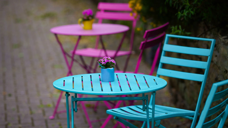 Blue Punch Seat Chair No People Absence Table Empty Focus On Foreground Plant Front Or Back Yard Food And Drink Day Wood - Material Furniture Nature Business Tablecloth Restaurant Outdoors Selective Focus Pink Color Glass Setting Purple Outdoor Chair Blue