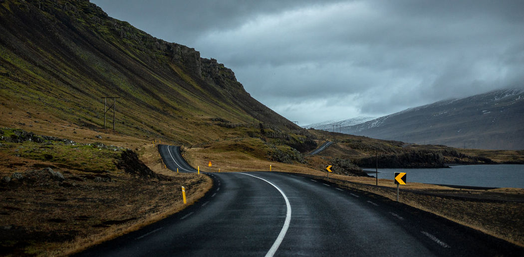 Dramatic winding road by mountain against sky