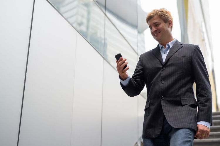 Low angle view of businessman standing by wall