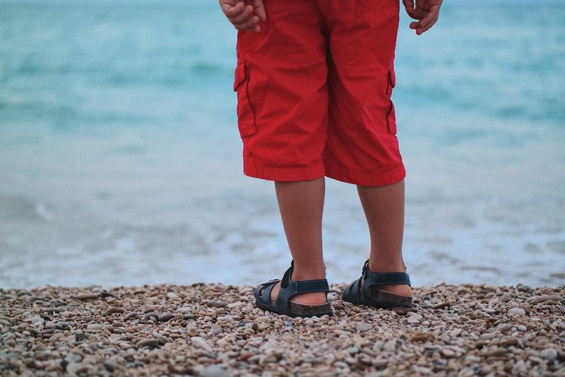 Low section of boy standing at beach