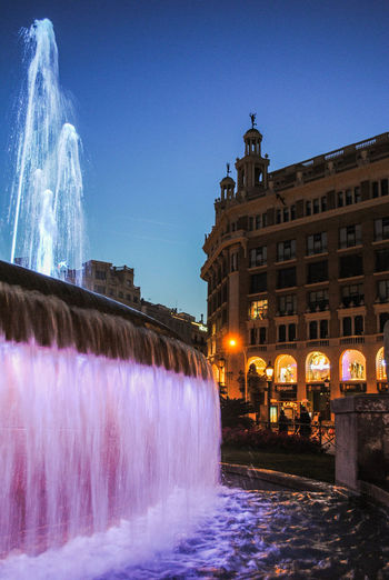 View of fountain against illuminated buildings at night