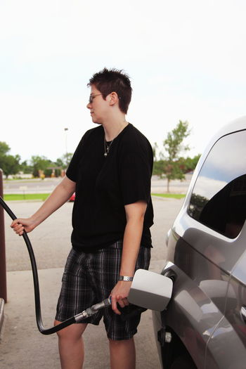 Woman Refueling Car At Gas Station