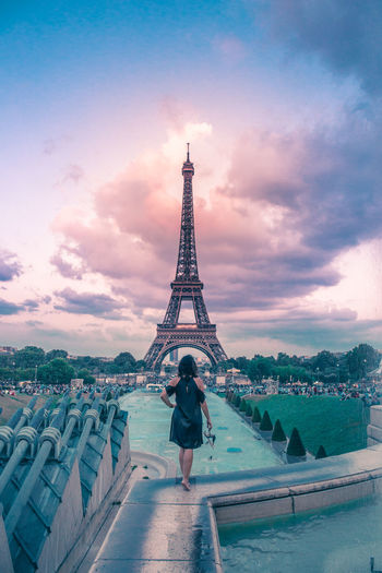 Rear view of woman looking at eiffel tower while standing on wall against cloudy sky