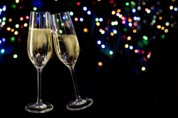 two champagne glasses in front of a dark background with colorful blurred bokeh lights, new year and party concept with copy space Champgne Glass Flute Two Objects Cheers Toast New Year Holiday Party Event Night Bokeh Lights Colorful Blurry Alcohol Drink Wine Food And Drink Copy Space Dark Sparkling Drinking Glass No People Indoors