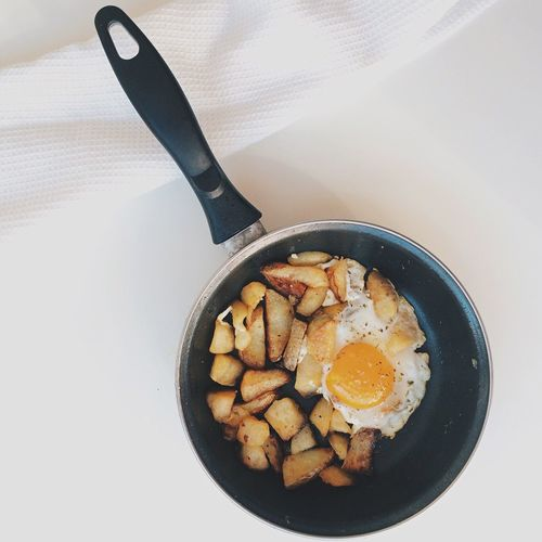 Directly Above View Of Egg And Fried Potatoes In Cooking Pan