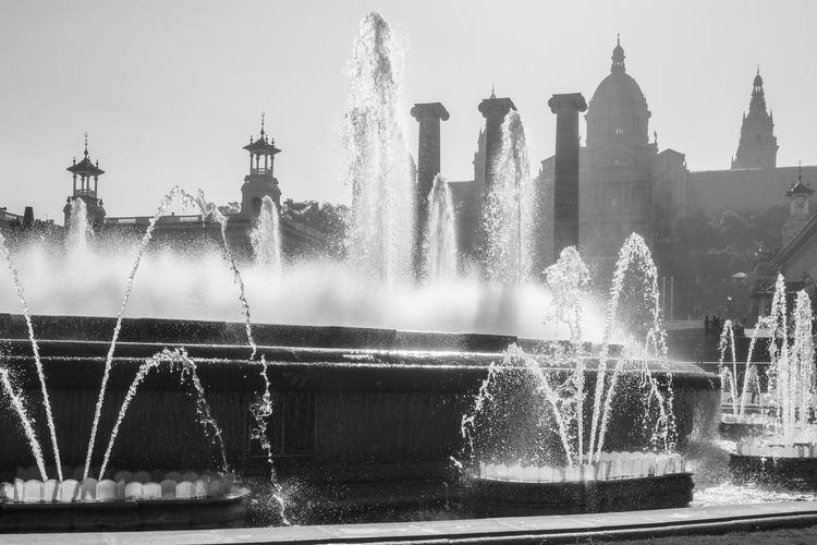Water splashing fountain against sky