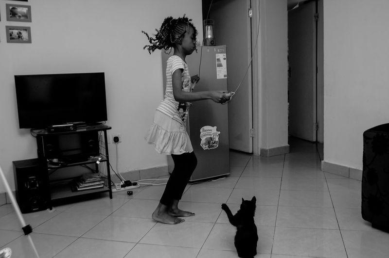 Full length of girl skipping on floor at home