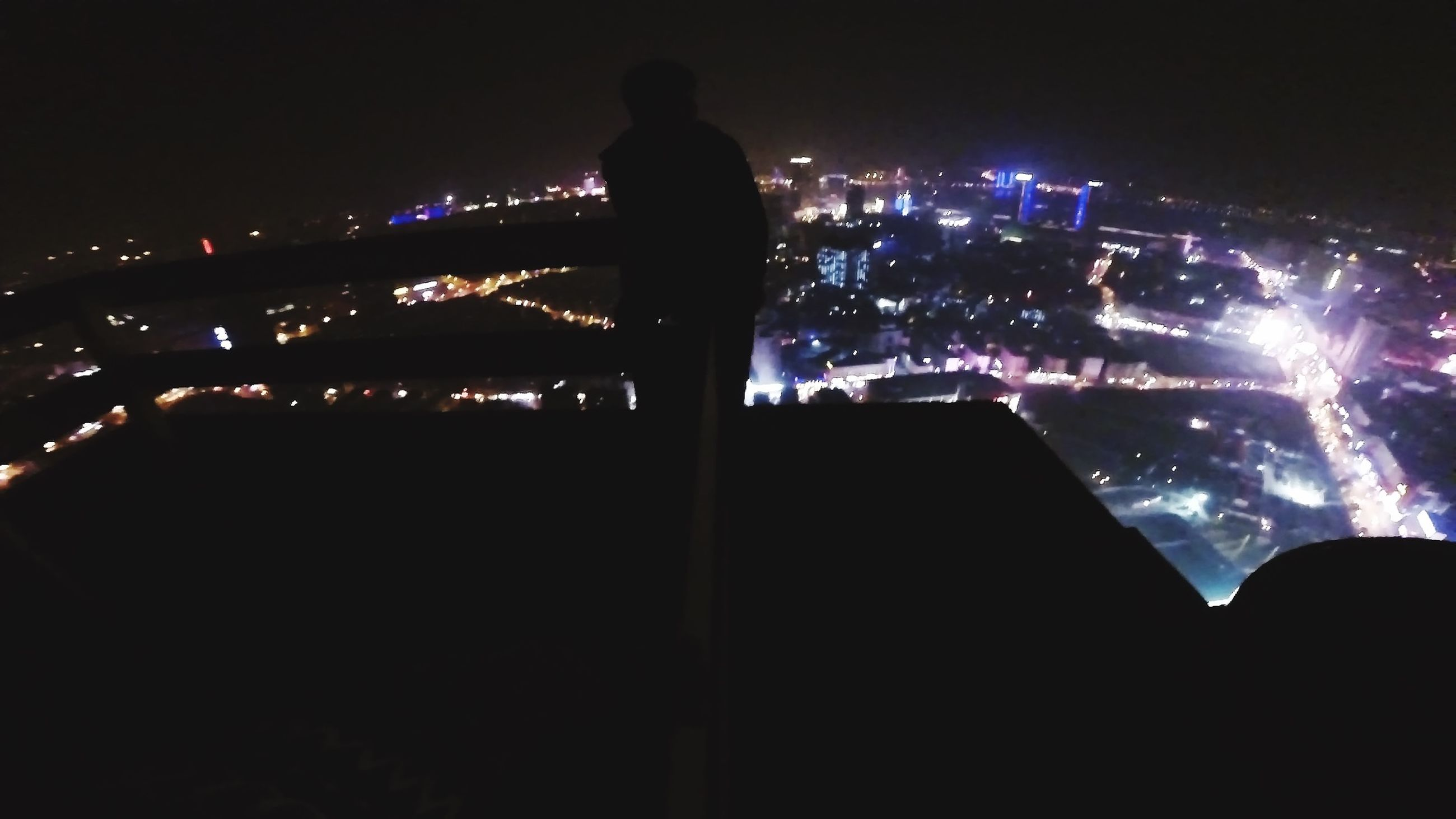night, illuminated, city, building exterior, architecture, silhouette, cityscape, built structure, lifestyles, dark, leisure activity, skyscraper, men, city life, water, modern, standing, rear view