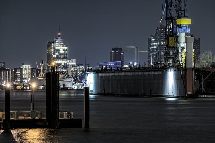 Illuminated port of hamburg in city at night