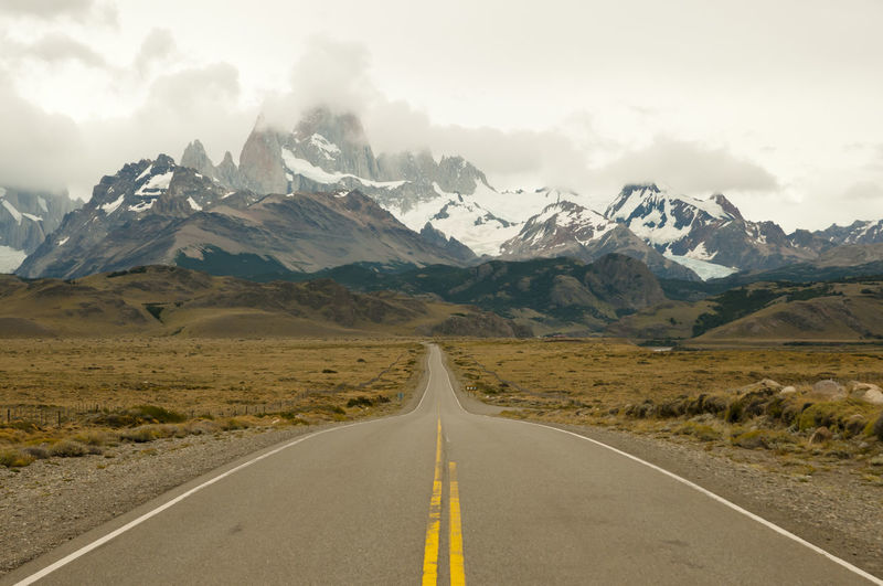 Empty road leading towards mountains during winter