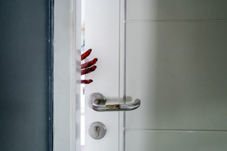 Cropped bloody hand of woman by door
