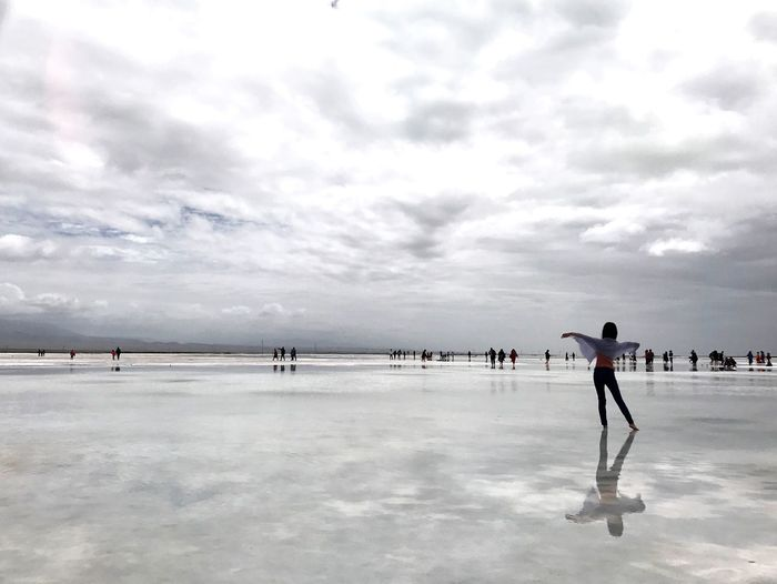 People playing in water against sky