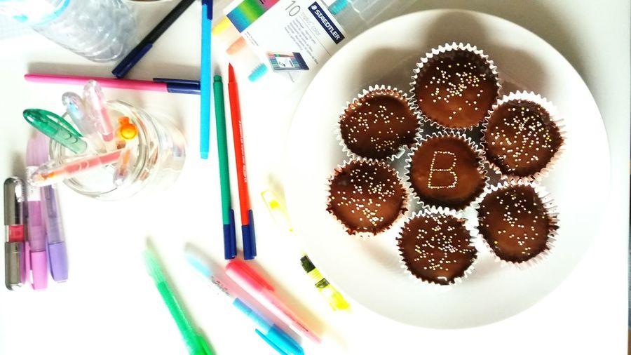 Directly above shot of felt tip pens and cupcakes on table