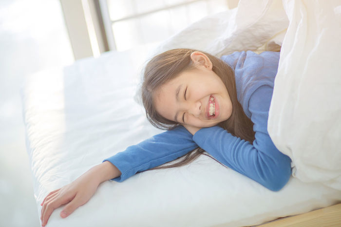Happy Asian girl in lazy day Asian  Japanese  Korean Bed Bedroom Cheerful Childhood Chinese Comfortable Cute Day Happiness Home Interior Innocence Lifestyles Lovely Lying Down Lying On Back People Pillow Portrait Real People Relaxation Sheet Smiling