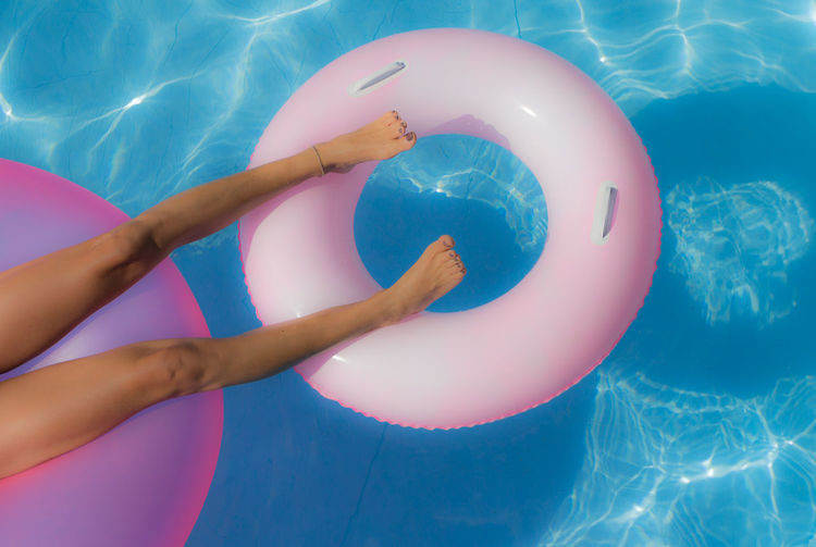 The pink life jacket floating in the pool and used to relax Blue Close-up Cropped Day Fun Leisure Activity Lifestyles Multi Colored Part Of Unrecognizable Person