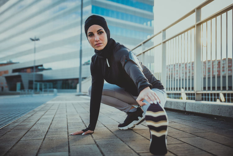Full length of beautiful woman wearing hijab exercising against building during sunrise