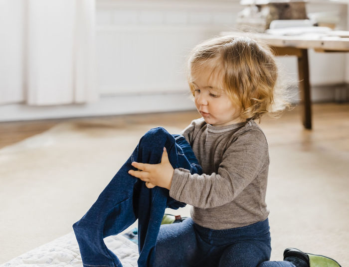 Cute Baby Girl Holding Jeans While Sitting On Floor At Home