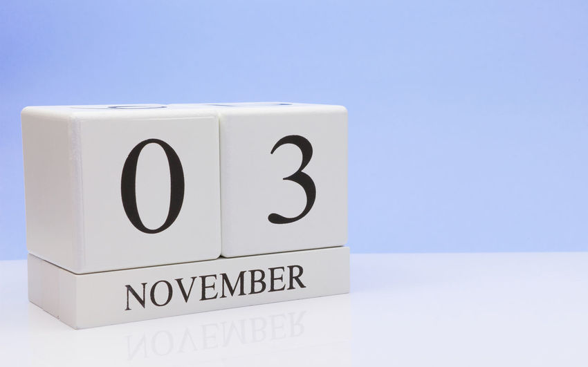 Close-up of november date on table against blue background