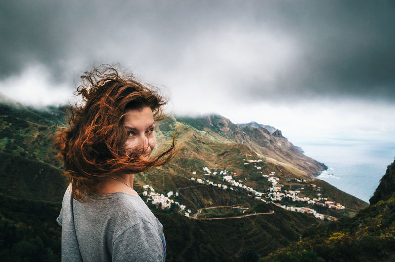 Joyful young woman with flying hair hidden her face looks at the camera in front of Taganana village on north of Tenerife. Traveler are enjoying the landscape, Canary Islands, Spain Canary Islands Beauty In Nature Casual Clothing Cloud - Sky Landscape Leisure Activity Mountain Mountain Range Nature One Person Outdoors Real People Scenics Standing Tenerife Village View Young Adult The Week On EyeEm Lost In The Landscape Go Higher Moments Of Happiness International Women's Day 2019