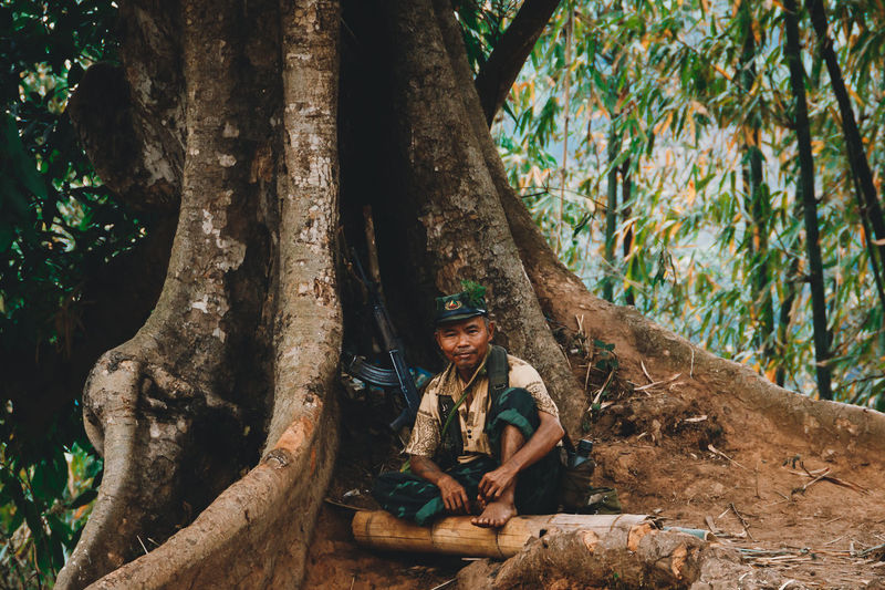 A rebel soldier sits under a banyan tree in the jungle of Myanmar. - IG @LostBoyMemoirs (Photos taken on Canon 650D Rebel T4i, edited in Lightroom.) People People Watching People Photography Streetwise Photography Street Photography ASIA Myanmar Burma Myanmar Culture Myanmarphotos Adventure Backpacking Culture And Tradition Cultures Exploration Travel Destinations Portrait Portrait Photography Military Soldier Rebel Army Tree Tree Trunk Trunk Plant Sitting Real People One Person Front View Nature Leisure Activity Day Lifestyles Forest Land Smiling Casual Clothing Happiness Males  Outdoors My Best Photo The Art Of Street Photography