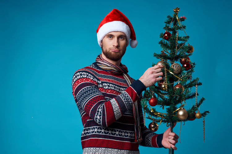 Portrait of man with christmas tree against blue background