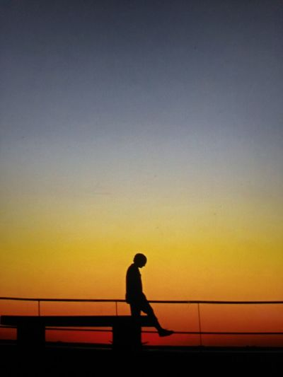 Silhouette man standing on bridge against sky during sunset