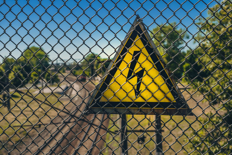 Close-up of chainlink fence against yellow sky