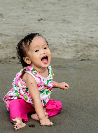 Portrait of cute girl sitting on sand at beach