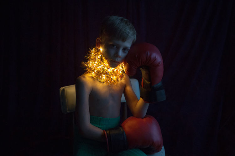 Portrait of shirtless boy with boxing gloves and illuminated lights around neck at home