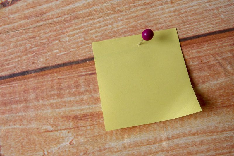 YELLOW STICKER STICK ON A WOODEN BACKGROUND Adhesive Note Blank Bulletin Board Close-up Copy Space Fruit Indoors  Message No People Note Office Paper Red Reminder Straight Pin Table Thumbtack Wall Wall - Building Feature Wood - Material Yellow