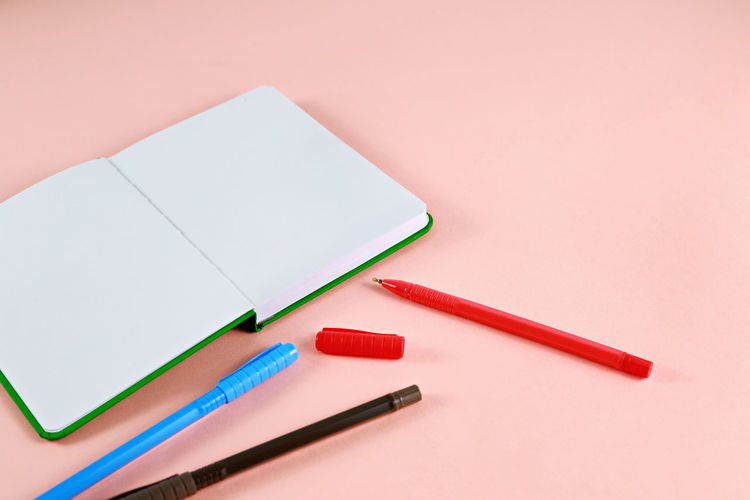 Close-up of diary and pens on pink background