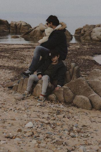 Men sitting on rock by land against sky