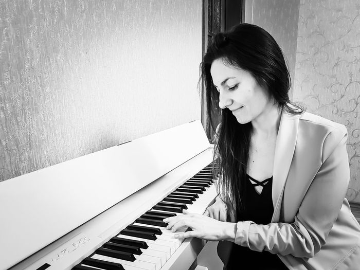 Young woman playing piano against wall