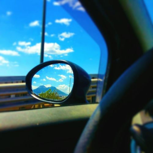 Close-up of side-view mirror against blue sky