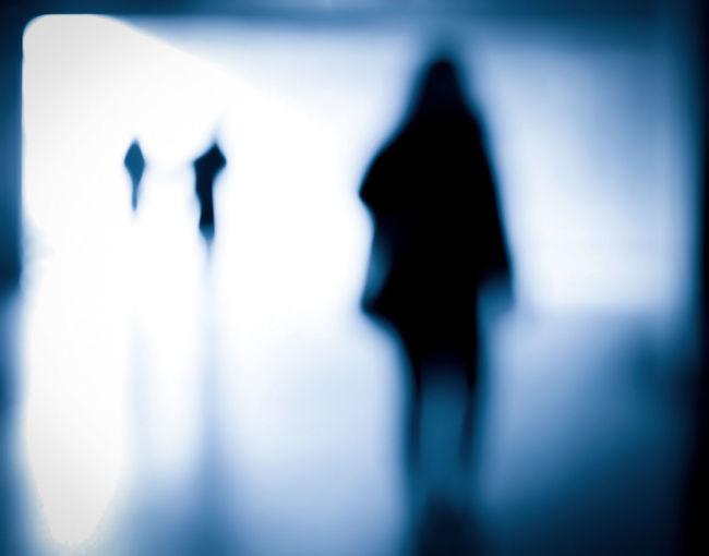 Defocused image of silhouette people standing against wall