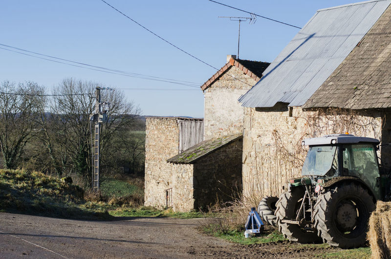A farm in rural France. Barn Farm Tractor Winter Architecture Blue Building Exterior Built Structure Day Electricity Pylon Field House Land Vehicle Mode Of Transport No People Outdoors Sky Technology Transportation Tree