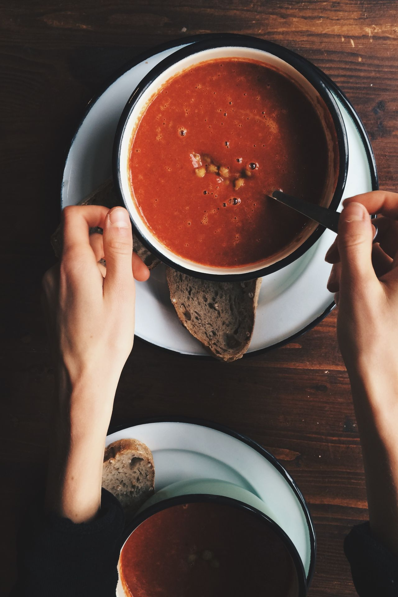 Cropped hands on woman with fresh soup on table