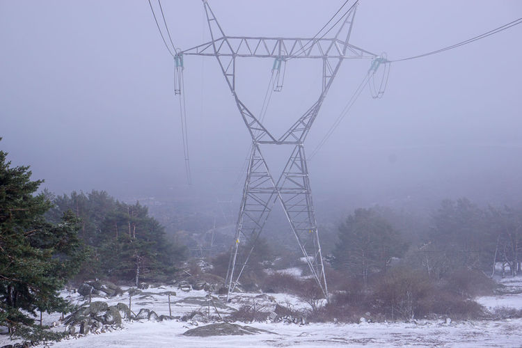 Electricity pylon on snow covered land against sky