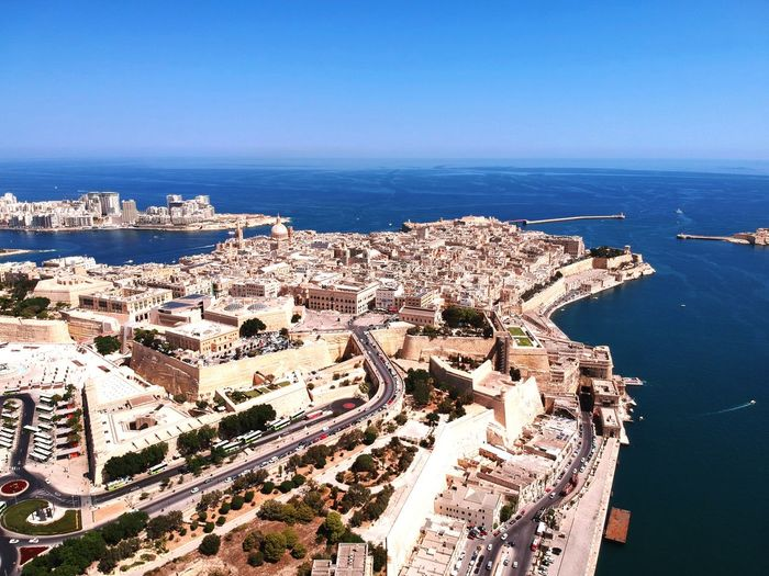 Aerial View Of Townscape By Sea Against Clear Sky During Sunny Day