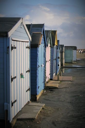 Beach huts on sand against cloudy sky