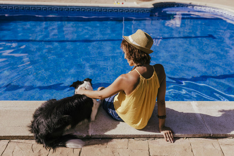 Rear view of woman sitting by swimming pool