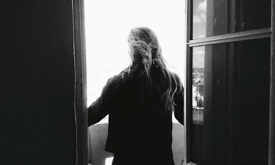 Window Indoors  Rear View Long Hair Standing Waist Up Person Three Quarter Length Home Interior Lifestyles Leisure Activity Day Young Adult Alone Contemplation Window Frame