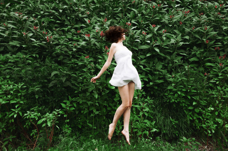 Woman jumping in grass