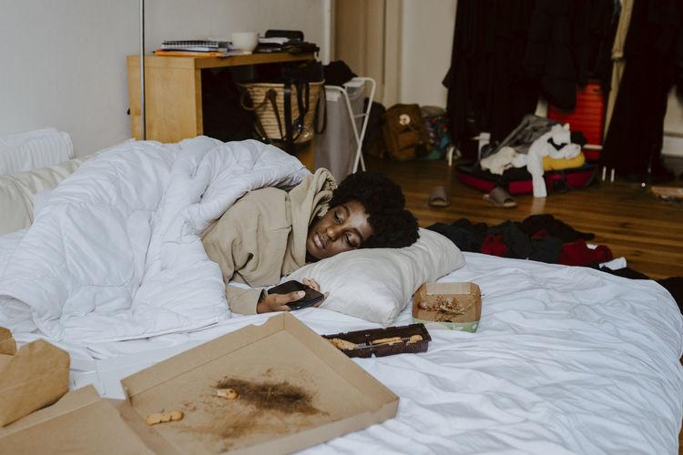 People relaxing on bed in bedroom
