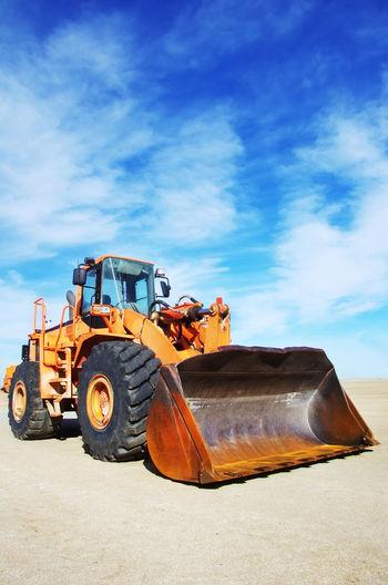 Bulldozer On Field Against Cloudy Blue Sky