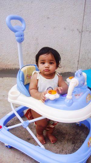 Portrait of cute toddler standing in baby walker