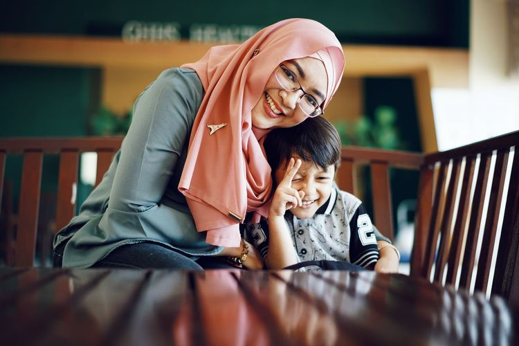 Portrait of mother smiling while sitting with son at table