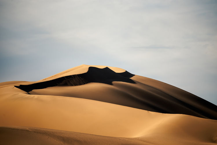 Low angle view of sand dune in desert against sky