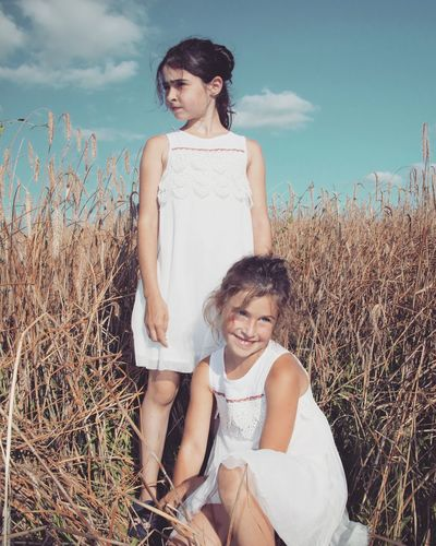 Sisters On Grassy Field Against Blue Sky