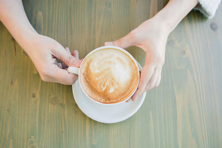 cappuccino Coffee Cup Food And Drink Refreshment Coffee Cup Drink Mug Coffee - Drink Human Hand Real People Hand Frothy Drink Table One Person Holding Human Body Part Lifestyles Leisure Activity Hot Drink Women Crockery Latte Finger